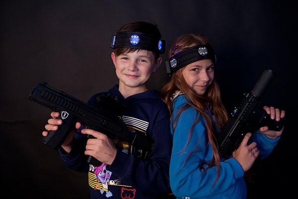 дети позируют с лазертаг оружием в развлекательном центре Фактория